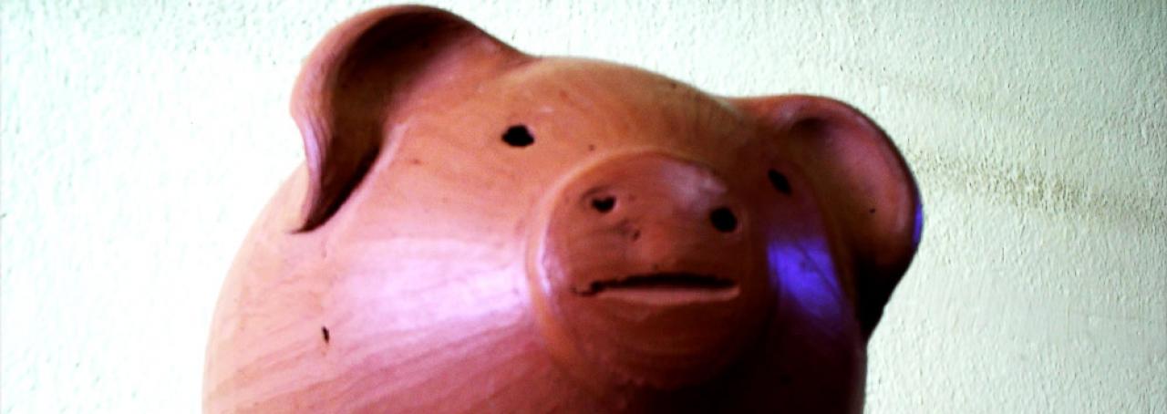 Cofrinho de porco em mesa de vidro