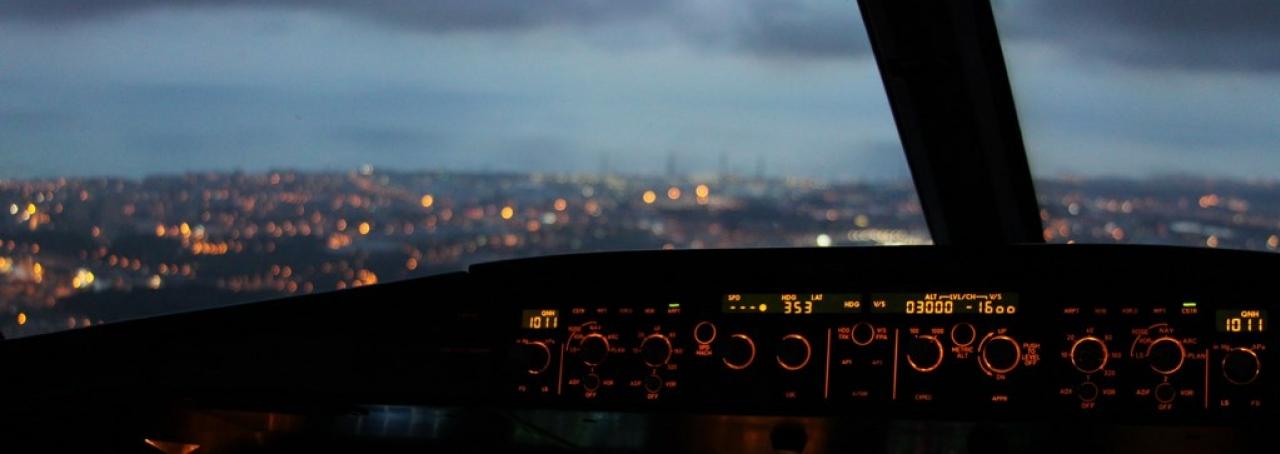 Cidade ao fundo. Janela de avião. Painel de instrumentos de avião
