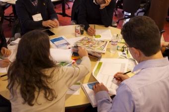 Pessoas reunidas em torno de uma mesa com vários papéis trabalhando.